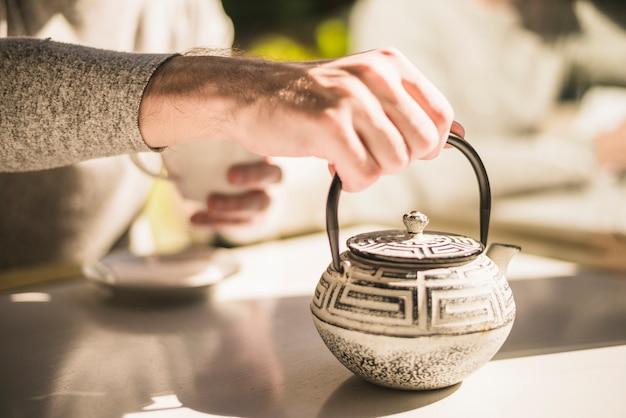 Nahaufnahme der hand traditionellen kessel auf tabelle halten