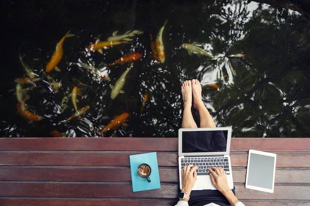 Nahaufnahme der hand unter verwendung des laptops und der tablette mit kaffeetasse