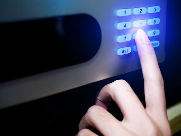 Nahaufnahme der hand zahlen mit passwort code der sperre auf safe drücken.