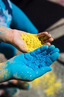 Nahaufnahme der hand zwei frauen, die gelbe und blaue holi farbe anhält