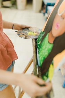 Nahaufnahme der handmalerei der frau mit ölfarbe auf gestell