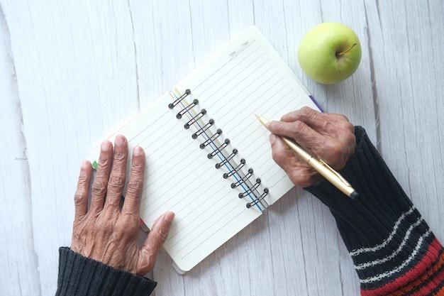 Nahaufnahme der handschrift der älteren frauen auf notizblock.