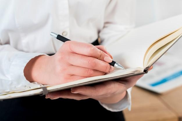 Nahaufnahme der handschrift der geschäftsfrau auf tagebuch mit stift