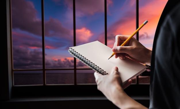 Nahaufnahme der handschrift einer frau macht sich notizen, während sie über dem büro steht