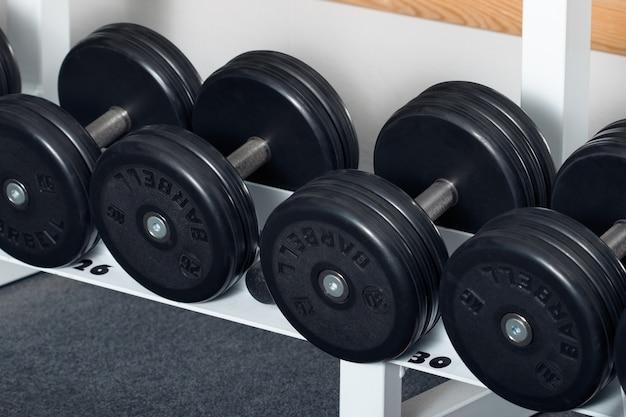 Nahaufnahme der hanteln, die in reihe an im fitnessstudio organisiert werden