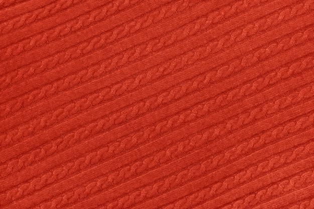 Nahaufnahme der hintergrundtextur aus rotem, gestricktem wolljersey-pullover mit reihengeflechtmuster