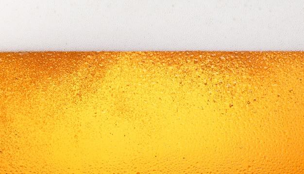 Nahaufnahme der hintergrundtextur des gießens von lagerbier mit blasen und schaum in frostigem glas mit tropfen, seitenansicht mit niedrigem winkel