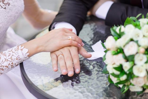 Nahaufnahme der hochzeitshände mit ringen und blumenstrauß liegen auf dem tisch