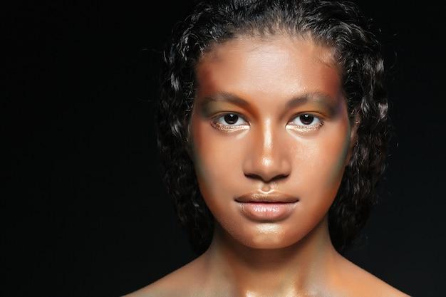 Nahaufnahme der hübschen amerikanischen jungen frau mit mode-make-up über schwarz
