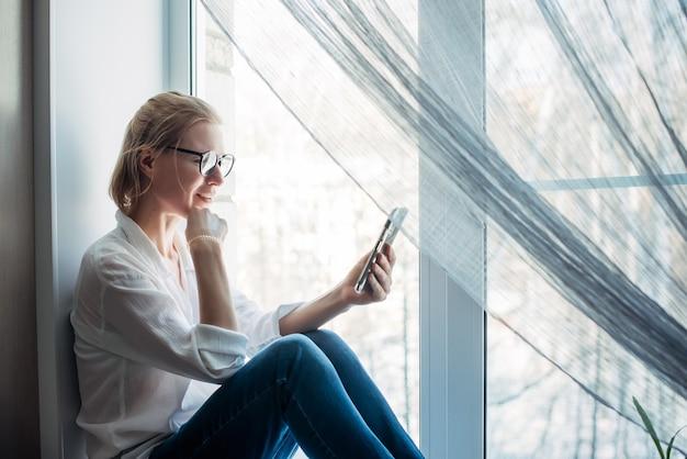 Nahaufnahme der hübschen frau, die zu hause auf einer fensterbank sitzt, mit smartphone in der hand. online-chat für frauen.
