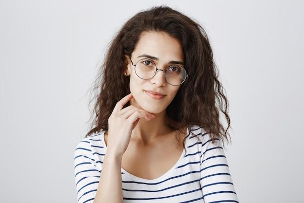 Nahaufnahme der hübschen frau in den gläsern, die mit interesse schauen