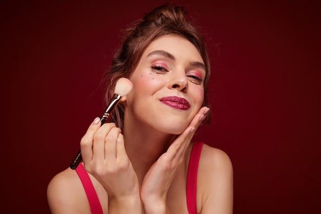 Nahaufnahme der hübschen jungen brünetten frau mit den bordeauxroten lippen, die errötungen auf ihren wangen anwenden, während sie sich auf die abendparty mit ihren freunden vorbereiten und posieren