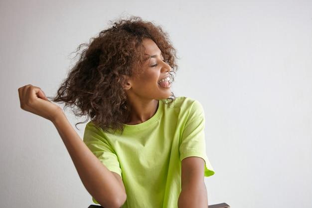 Nahaufnahme der hübschen jungen dunkelhäutigen frau, die mit geschlossenen augen sitzt und ihr lockiges haar zieht, spaß macht und zunge zeigt