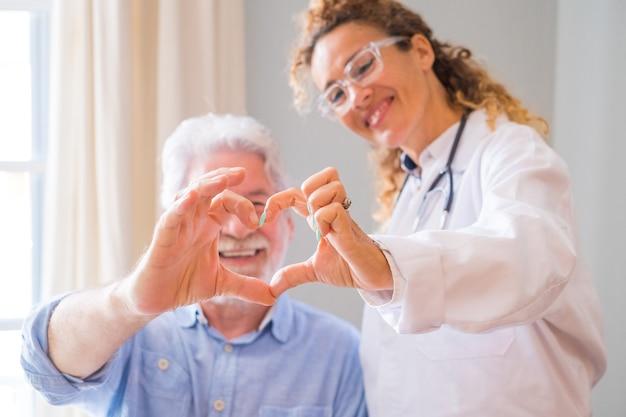 Nahaufnahme der jungen ärztin und des älteren mannes, die zu hause herzzeichen mit der hand zeigen. arzt hilft älteren patienten und kümmert sich. medizinische versorgung älterer menschen.