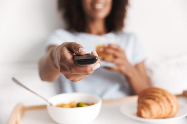 Nahaufnahme der jungen afrikanischen frau, die fernsehfernbedienung hält