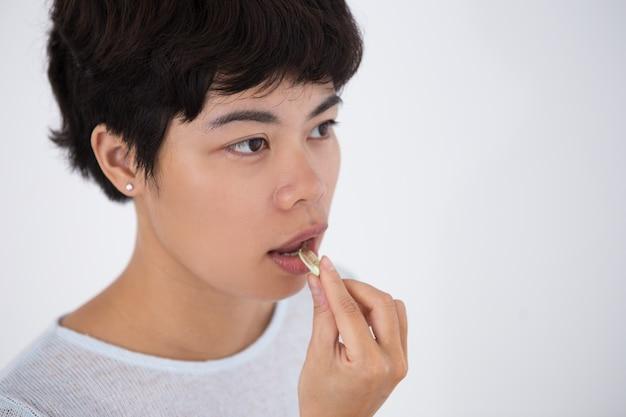 Nahaufnahme der jungen asiatischen frau, die pille nimmt