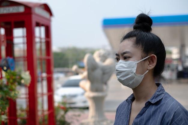 Nahaufnahme der jungen asiatischen frau stehend, die eine atemschutzmaske n95 aufsetzt, um vor luftgetragenen atemwegserkrankungen zu schützen