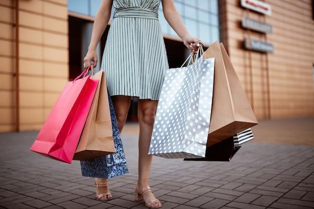 Nahaufnahme der jungen attraktiven frau, die einige einkaufstaschen mit neu gekauften waren und kleidern hält.