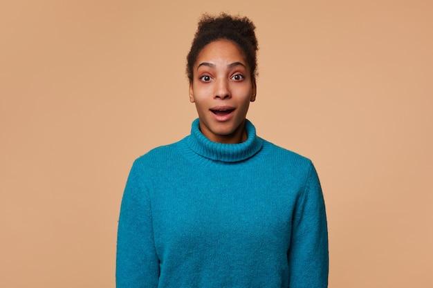 Nahaufnahme der jungen benommenen afroamerikanischen dame mit dem lockigen dunklen haar, das einen blauen pullover trägt, hörte die unglaublichen nachrichten. weit offener mund und blick auf die kamera isoliert über beigem hintergrund.