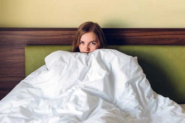 Nahaufnahme der jungen blonden frau, die sich verärgert, traurig, enttäuschend weinen einsam im grünen schlafzimmer fühlt. emotionaler schock und lebensprobleme, häusliche gewalt
