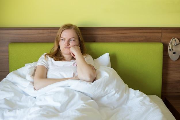 Nahaufnahme der jungen blonden frau, die sich verärgert, traurig, enttäuschend weinen einsam im grünen schlafzimmer fühlt. emotionaler schock und lebensprobleme mit partner im bett