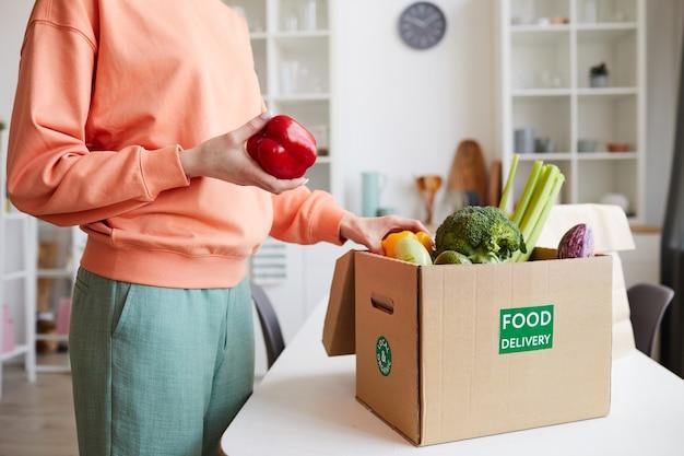 Nahaufnahme der jungen frau, die das frische gemüse aus der schachtel auspackt, während in der häuslichen küche steht