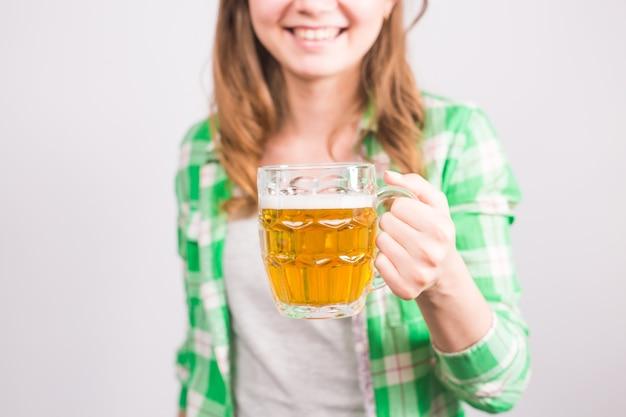 Nahaufnahme der jungen frau, die einen bierkrug voll bier hält und auf weißem hintergrund lächelt