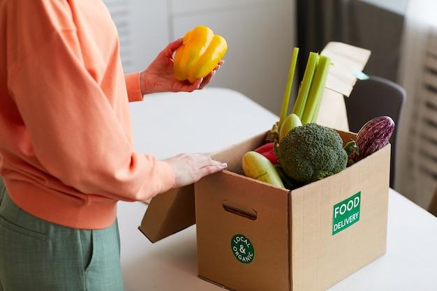 Nahaufnahme der jungen frau, die frisches gemüse aus der schachtel in der küche nimmt