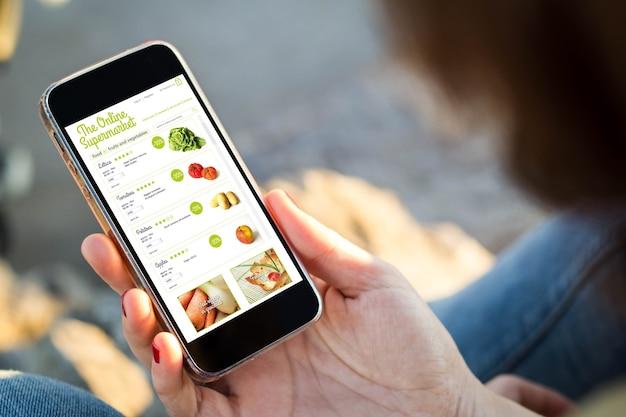 Nahaufnahme der jungen frau, die lebensmittel auf online-supermarkt mit ihrem handy einkauft.