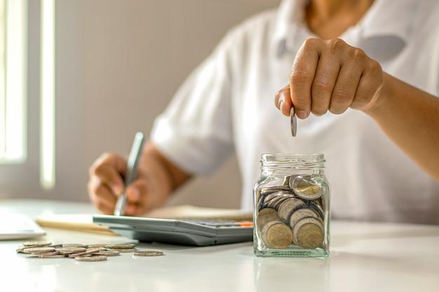 Nahaufnahme der jungen frau, die münze in eine flasche setzt, geld spart, geldsparkonzept für finanzbuchhaltung.