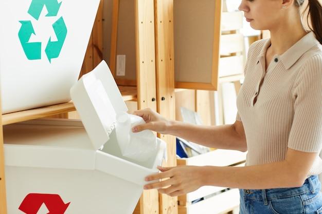 Nahaufnahme der jungen frau, die plastikflaschen in die behälter für müll recycelt