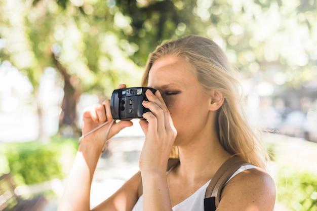 Nahaufnahme der jungen frau fotografierend mit moderner digitalkamera