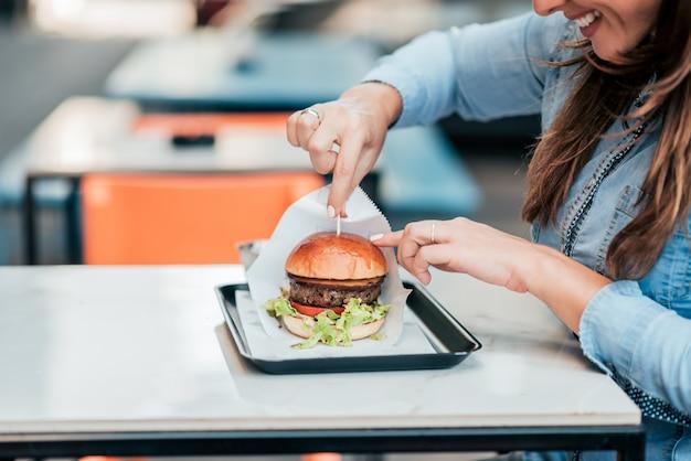 Nahaufnahme der jungen frau hamburger essend.