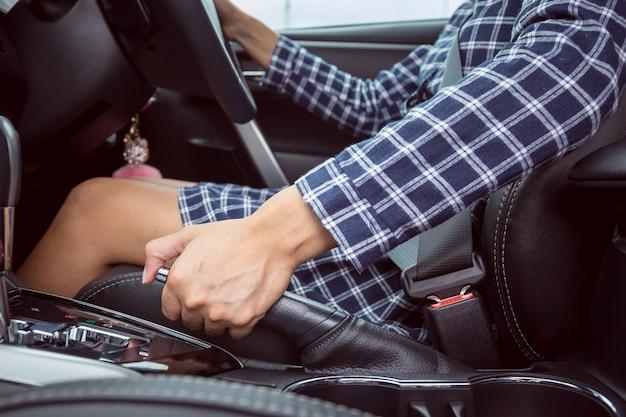 Nahaufnahme der jungen frau handbremsenhebel im auto ziehend
