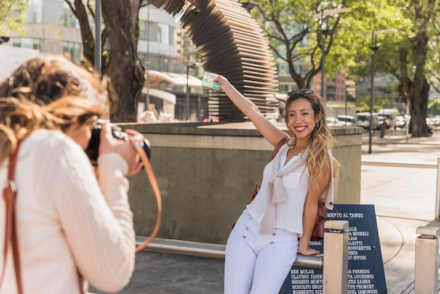 Nahaufnahme der jungen frau ihre freundin fotografierend, die ihre arme zeigt karte anhebt