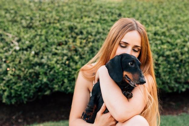 Nahaufnahme der jungen frau ihren hund umfassend