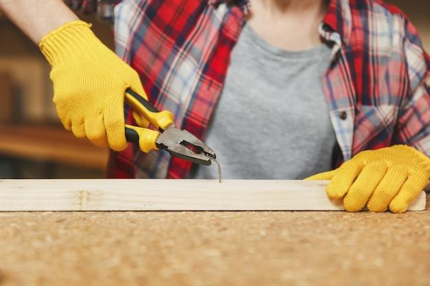 Nahaufnahme der jungen frau im karierten hemd, grauem t-shirt, gelben handschuhen, die in der tischlerei am holztisch mit verschiedenen werkzeugen arbeiten und den nagel mit einer zange herausnehmen, nachdem er in das brett gehämmert wurde.