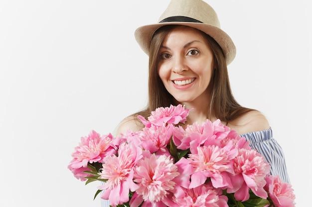 Nahaufnahme der jungen frau im kleid, hut hält bouquet von schönen rosa pfingstrosen blumen isoliert auf weißem hintergrund. valentinstag, internationaler frauentag-feiertagskonzept. werbefläche.