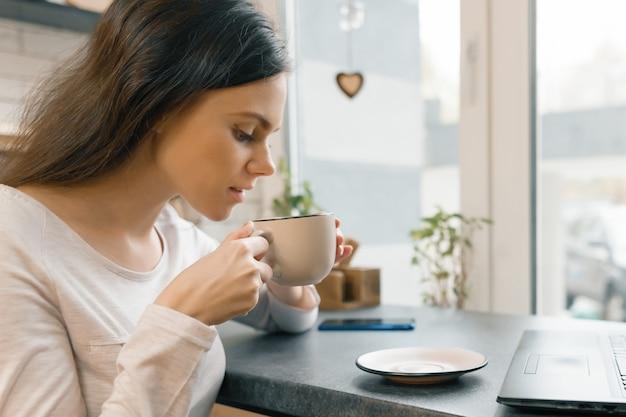 Nahaufnahme der jungen frau im profil mit schale frischem kaffee in der kaffeestube