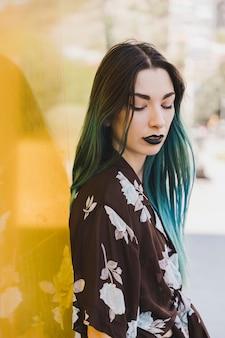 Nahaufnahme der jungen frau mit dem gefärbten haar, das vor gelbem reflektierendem hintergrund steht