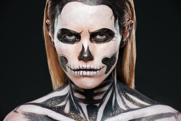 Nahaufnahme der jungen frau mit furchterregendem skelett make-up auf schwarzem hintergrund