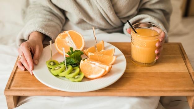 Nahaufnahme der jungen frau mit platte von früchten und von orangensaft auf hölzernem behälter