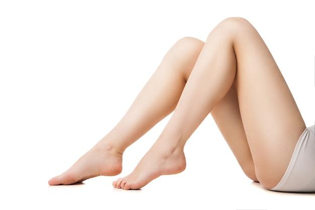 Nahaufnahme der jungen frau mit schönen beinen, die vor weißem hintergrund liegen