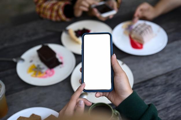 Nahaufnahme der jungen frau mit smartphone, das foto von süßem dessert macht.