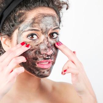 Nahaufnahme der jungen Frau schwarze Gesichtsmaske mit ihren Fingern anwendend