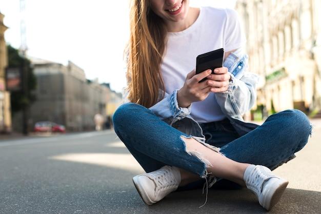 Nahaufnahme der jungen frau sitzend auf straße unter verwendung des mobiltelefons