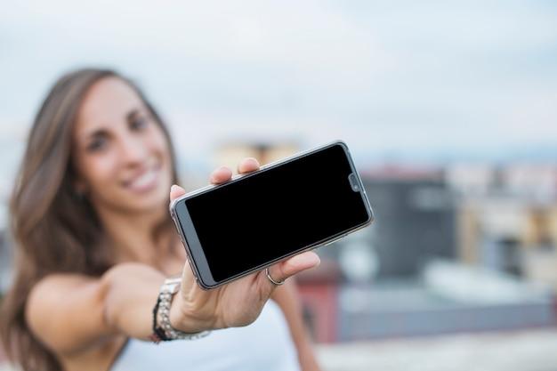 Nahaufnahme der jungen frau smartphone-bildschirm zeigend