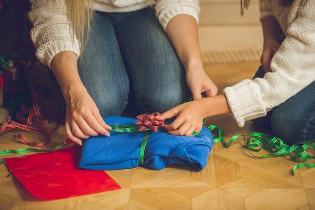 Nahaufnahme der jungen frau und des mädchens, die pullover in dekorativem papier und bunten bändern einwickeln