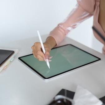Nahaufnahme der jungen geschäftsfrau, die ihre aufgabe auf mock-up-tablette im büroraum schreibt