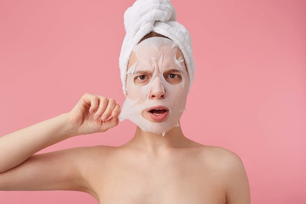 Nahaufnahme der jungen getrennten frau mit einem handtuch auf dem kopf nach dem duschen, das versucht, die stoffmaske vom gesicht zu entfernen, steht.